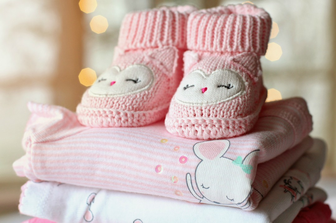 A photograph of some pink folded baby clothes and booties - Top Tips For Budgeting When Pregnant - Mrs H's favourite things