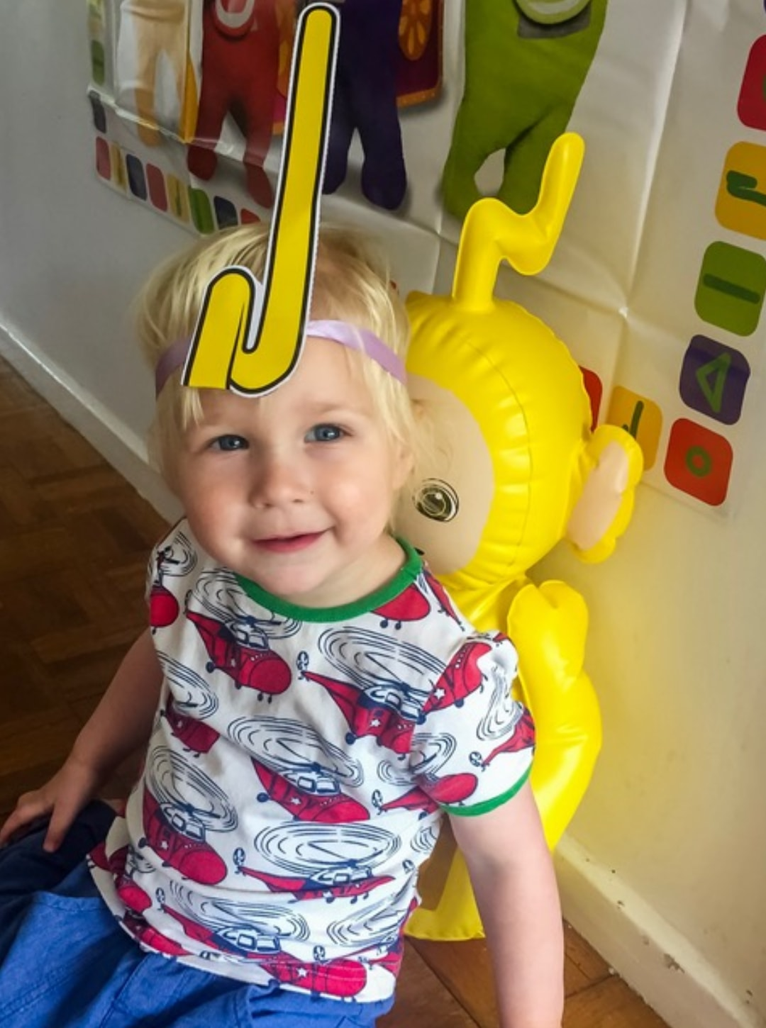 A photograph of a little boy sitting in front of the Teletubbies Custard Chaos Game and in front of the Inflatable Laa-Laa Bopper and wearing a Laa-Laa Tubby Antennae which is part of the Teletubbies Playdate Pack - Hosting A Teletubbies Playdate #TubbyPlaydate - Mrs H's favourite things