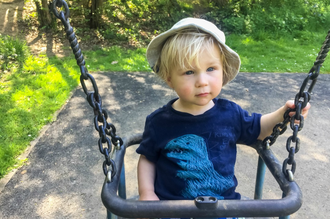 A photograph of a blonde little boy in a swing on a sunny day in the park - Our Weekend Happy 13: Country Parks, Woodland Walks and a Birthday Party - Mrs H's favourite things