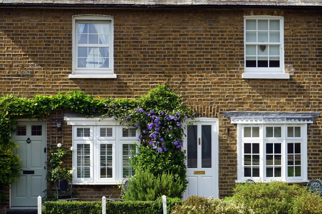 A photo of a pretty house with flowers around the door - Creating A Homely Vibe That Will Make The Whole Family Happy - Mrs H's favourite things