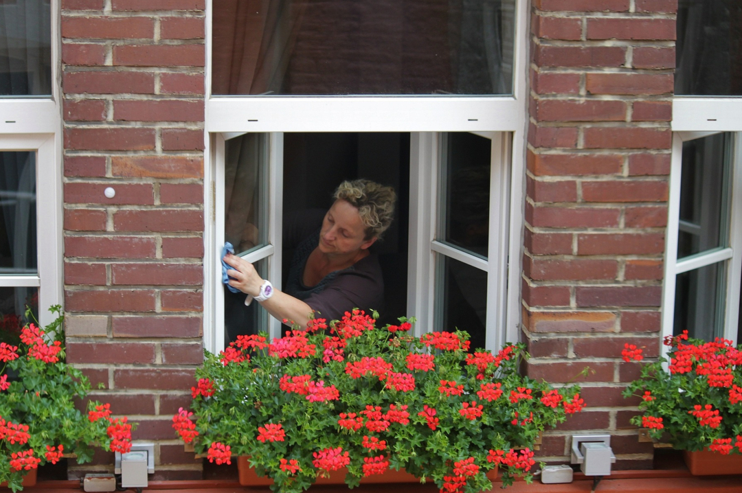 A photograph of a woman washing the windows of her house - Essential Summer Home Care For Year-Round Protection - Mrs H's favourite things