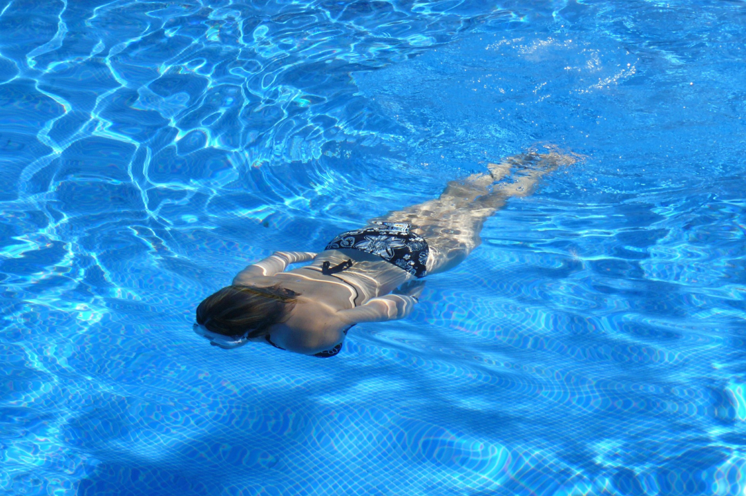 A photograph of a girl swimming in a bright blue swimming pool - Living The Dream: Having A Swimming Pool In Your Back Garden - Mrs H's favourite things