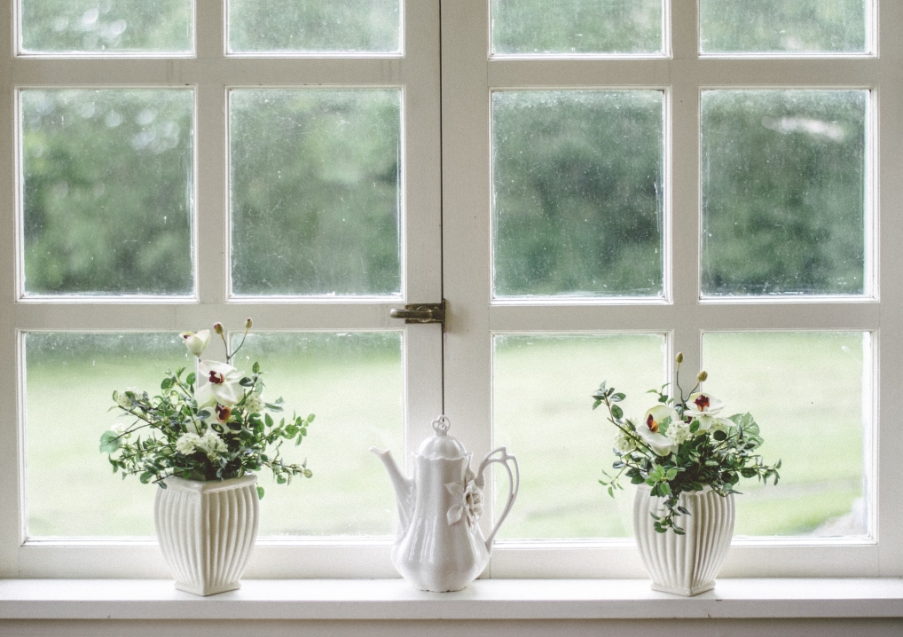 A photograph of a bright white window with two white planters with flowers and a white coffee pot - Practical Home Upgrades That Add Value & Look Chic - Mrs H's favourite things