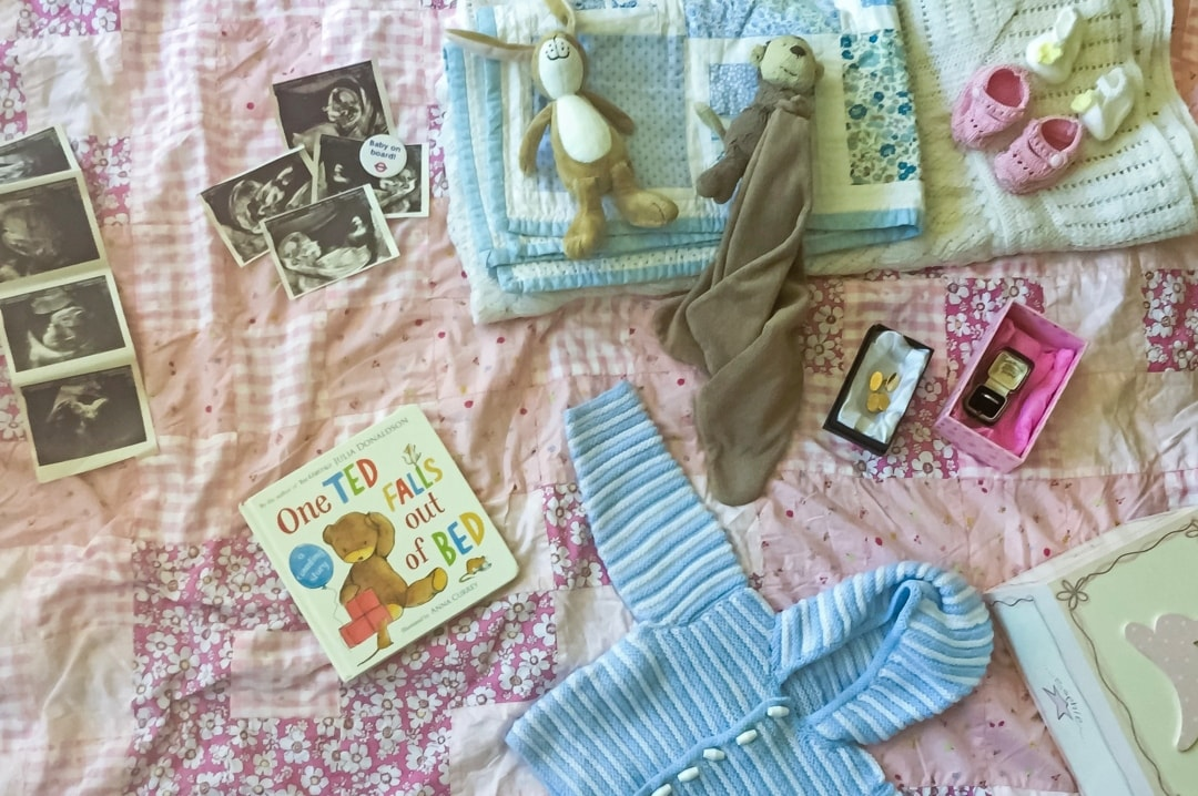 A photograph of a collection of baby items including blankets, first toys, knitted booties, favourite book, scan photos and baby on board badge - Store Your Memories With Bed Guru Ottoman Beds - Mrs H's favourite things
