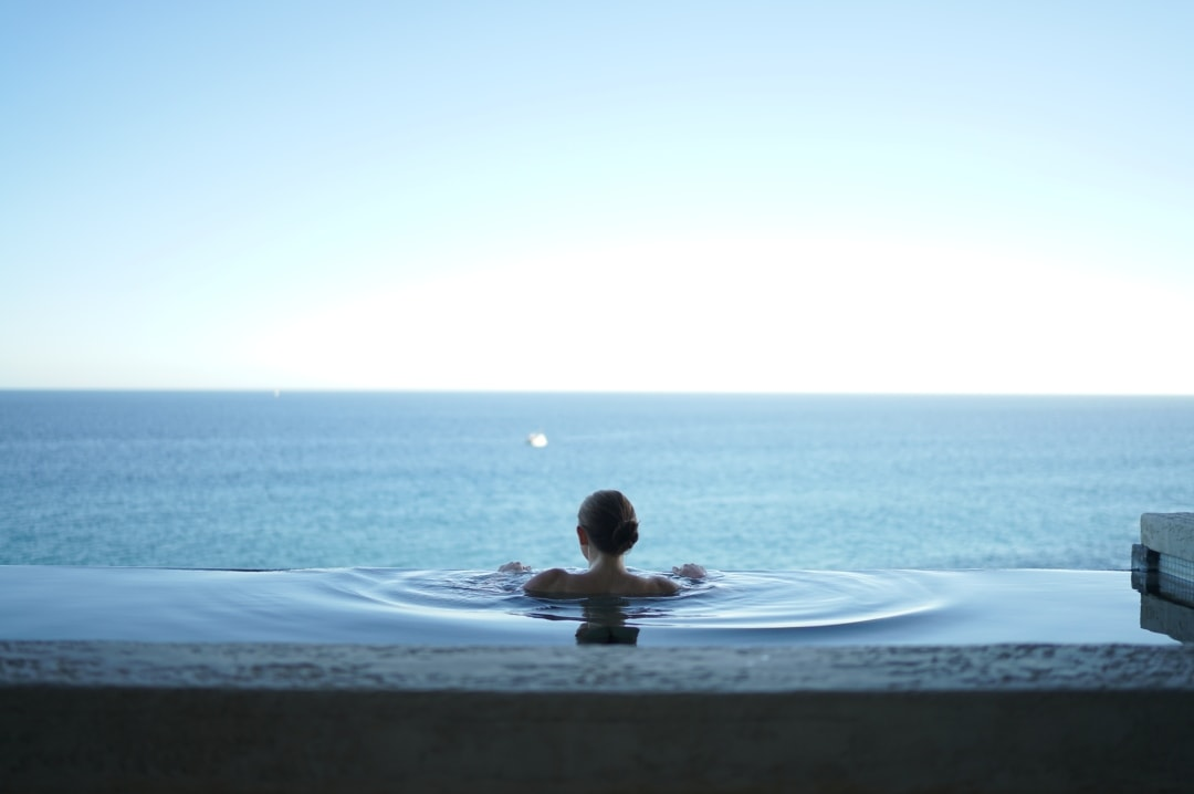 A woman in an infinity pool abroad on her babymoon - What Is A Babymoon? 5 Reasons Why You Should Have One - Mrs h's favourite things