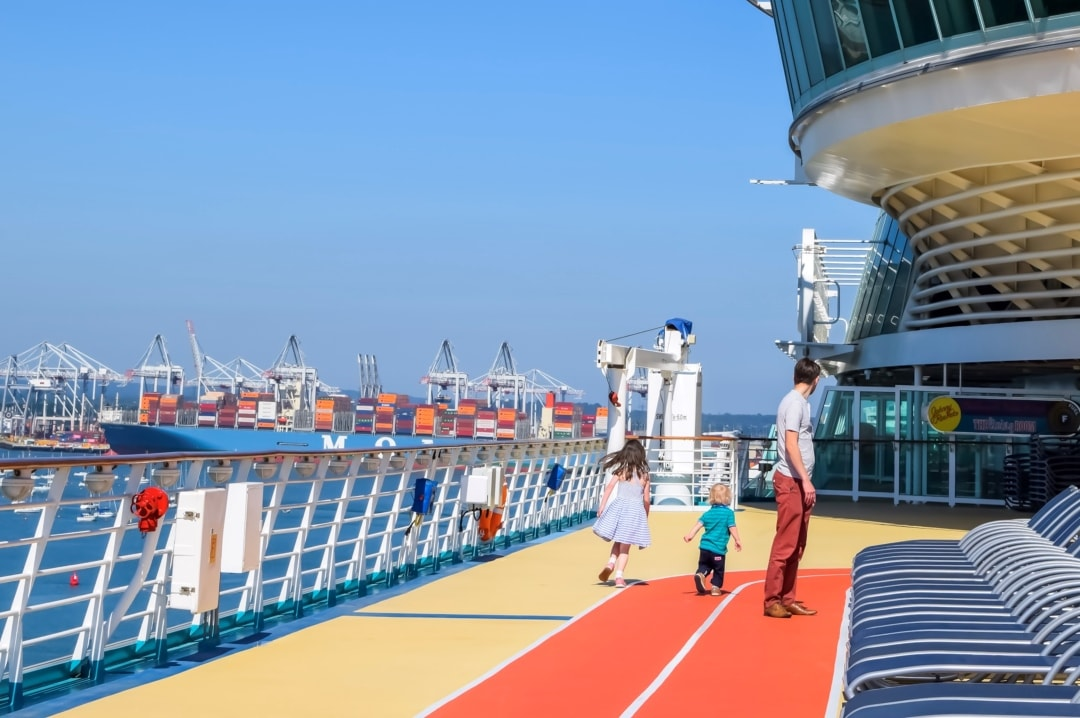 A photograph of a man, his young son and daughter walking on the top deck of the Royal Caribbean Cruise Ship - 10 Reasons Why A Royal Caribbean Cruise Would Make A Perfect Family Holiday - Mrs H's favourite things