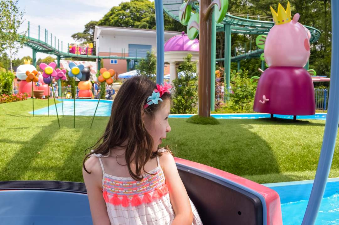 A photograph of a little girl on the ride Grampy Rabbit's Sailing Club and looking excitedly at a character from Peppa Pig - Paultons Park and Peppa Pig World - A Review - Mrs H's favourite things