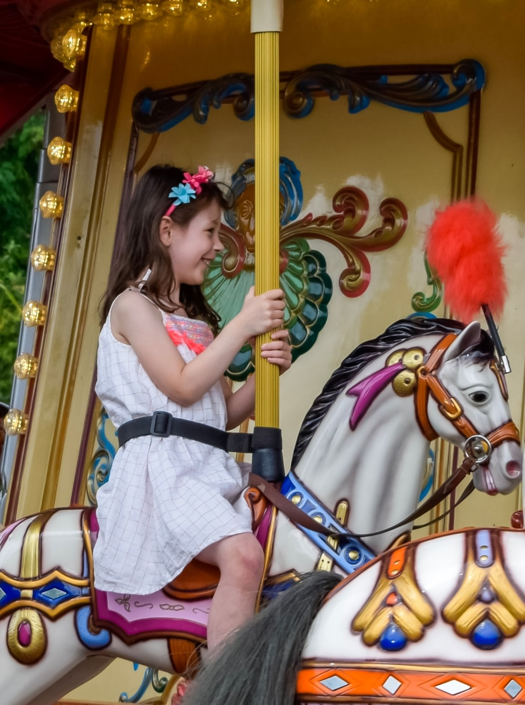A photograph of a little girl smiling on a Victorian carousel at Paultons Park - Paultons Park and Peppa Pig World - A Review - Mrs H's favourite things