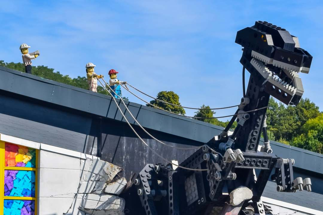 A photograph of a statue of a LEGO dinosaur being restrained by little LEGO men who stand on the roof of the building at LEGOLAND® Windsor Resort - LEGOLAND® Windsor Resort - Mrs H's favourite things