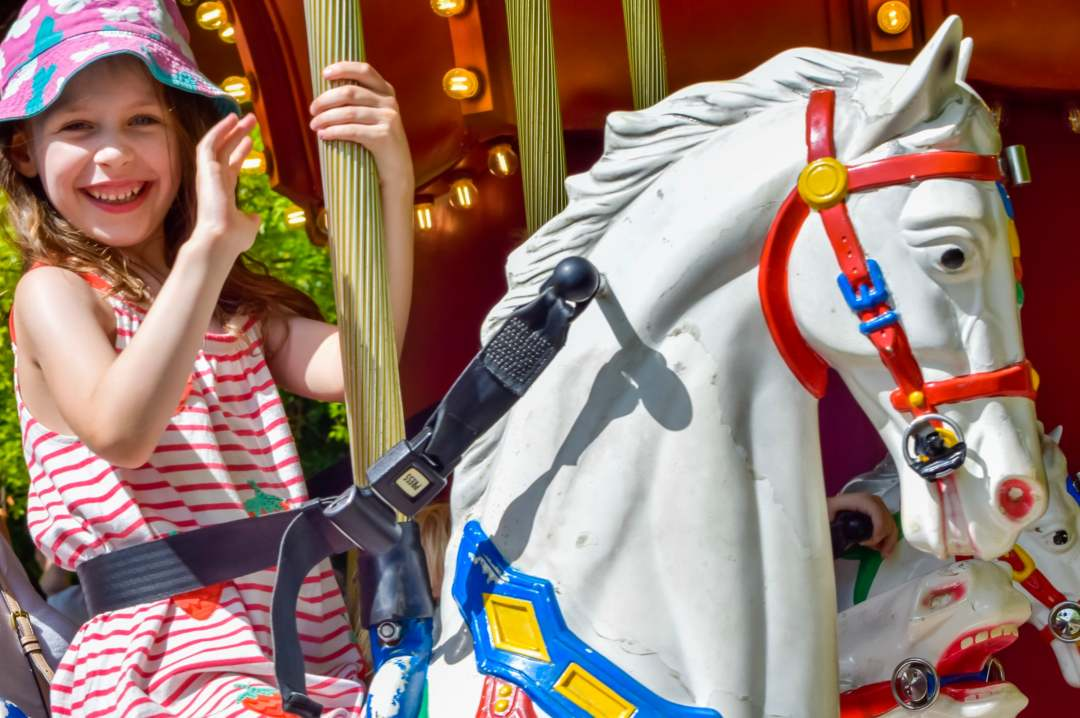 A photograph of a little girl on the Desert Chase carousel ride at LEGOLAND Windsor Resort - A Review - Mrs H's favourite things