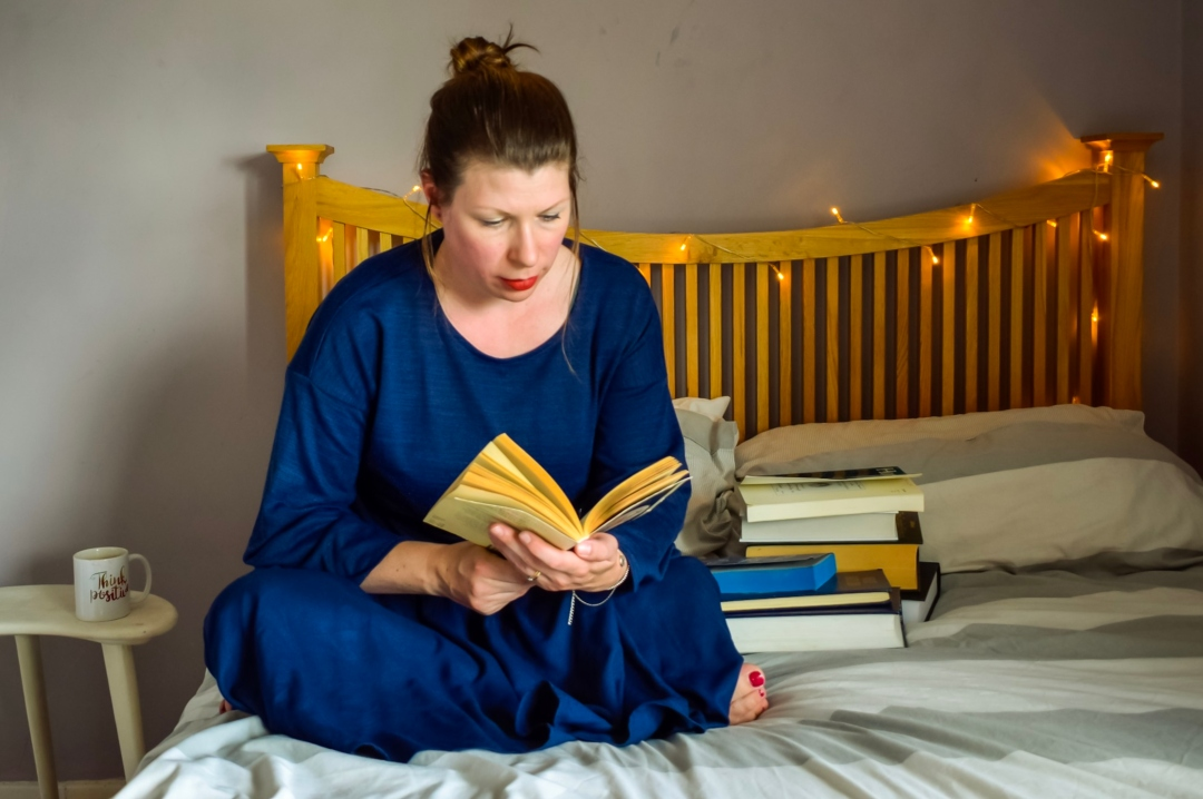 A photograph of a woman sitting on a bed and reading a book - Am I inspiring? A Post About Being A Finalist In The Britmums Brilliance in Blogging Awards - #BiBs2018 - Mrs H's favourite things