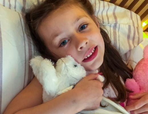 A photograph of a little girl cuddling her favourite softtoys and wrapped in a baby's blanket - Comforting Your Child's Eczema With Oilatum - #NationalEczemaWeek - Mrs H's favourite things