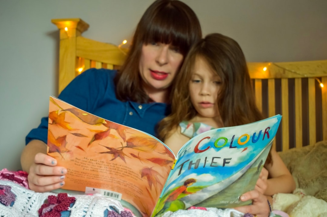 A photograph of a mother reading the book The Colour Thief to her daughter in bed - Taking Time To Read With Little Miss H And The BookTrust - Mrs H's favourite things