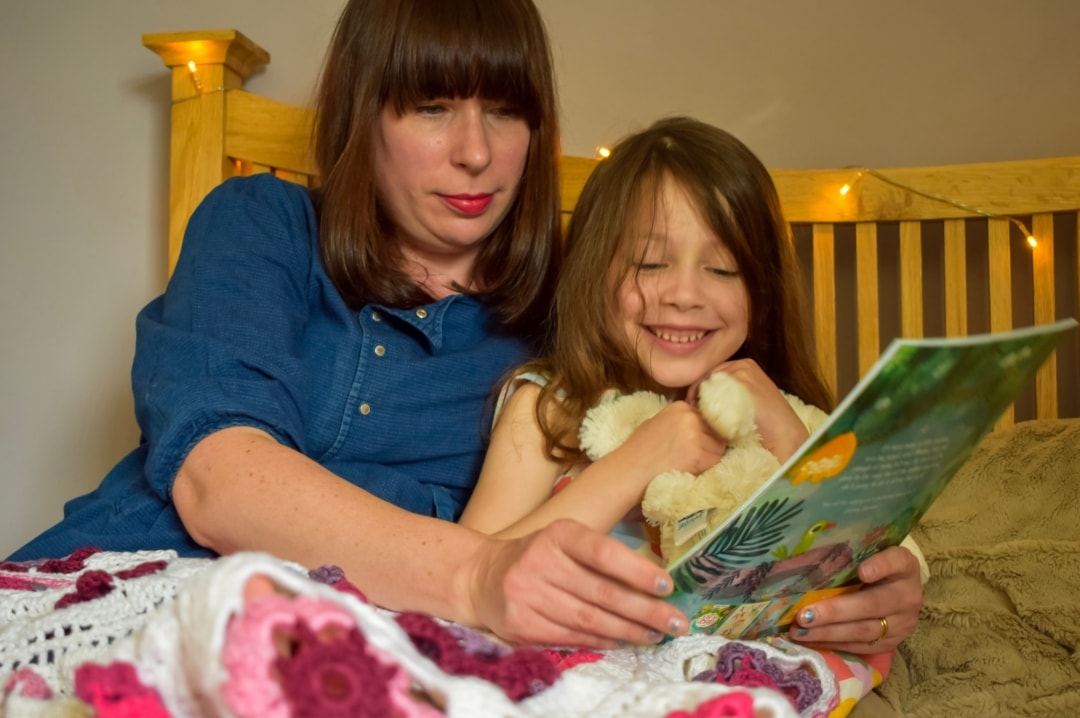 A photograph of a mother reading the Time To Read book Little Monkey to her daughter in bed - Taking Time To Read With Little Miss H And The BookTrust - Mrs H's favourite things