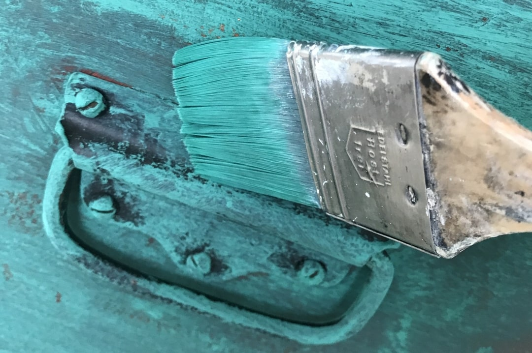 A photograph of someone painting a piece of furniture a teal colour - 4 Affordable Ways To Breathe New Life Into Your Home - Mrs H's favourite things