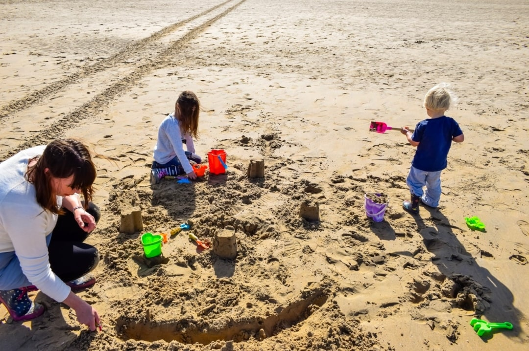A photograph of a mother with her son and daughter building sandcastles on a beach - Finding Happiness and Chasing Rainbows - September 2018 - Mrs H's favourite things