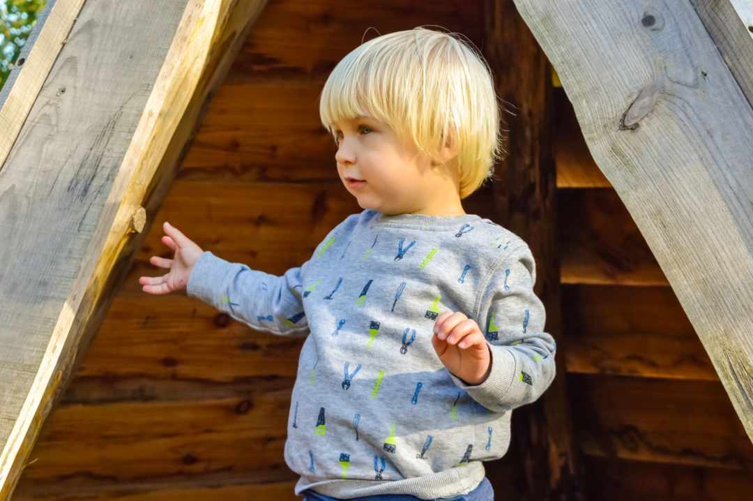 A photograph of a little boy playing in a wooden teepee at Slimbridge Wetlands Centre - Finding Happiness And Chasing Rainbows - October 2018 - Mrs H's favourite things