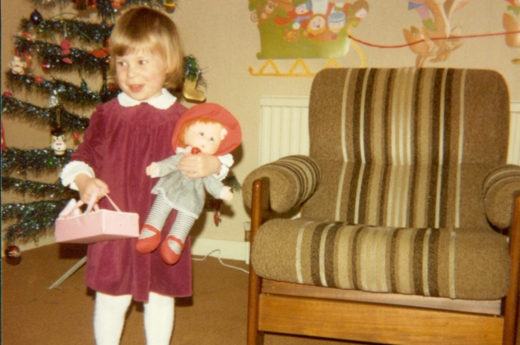 A photograph of a little girl standing in front of a Christmas tree and holding a doll - The Christmas Tag - Mrs H's favourite things