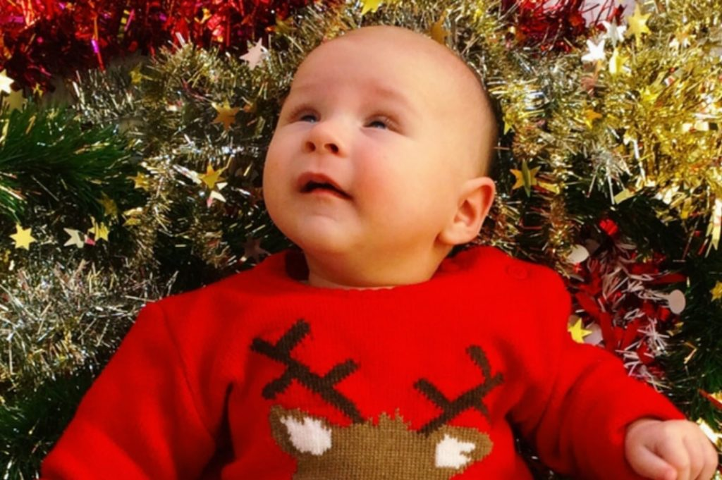 A photograph of a baby boy surrounded by tinsel and wearing a Christmas jumper - The Christmas Tag - Mrs H's favourite things