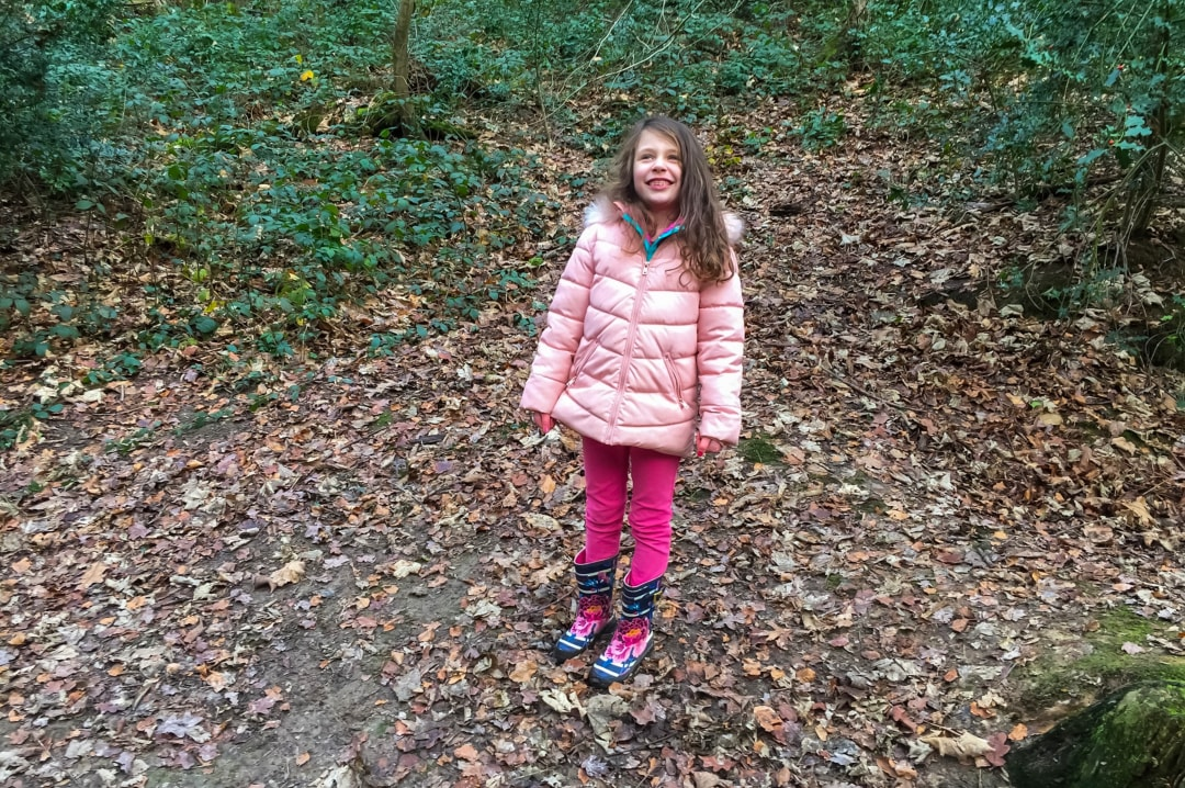 A photograph of a little girl going for a walk in the wood and beaming in happiness - Finding Happiness and Chasing Rainbow January 2019 - Mrs H's favourite things