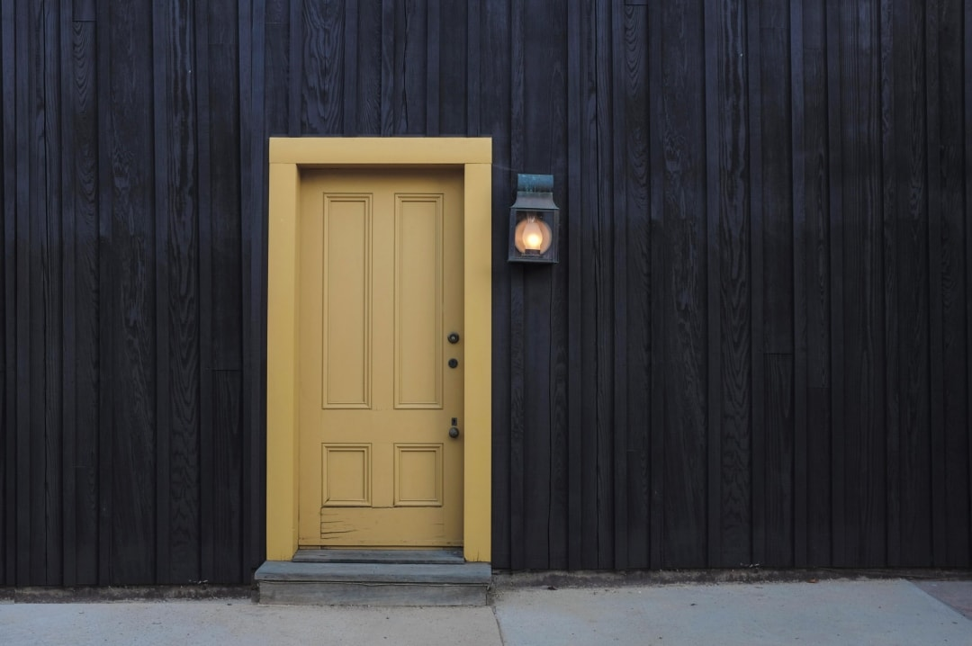 A photograph of a yellow door in a grey house - Preparing Your Home To Move Out - Mrs H's favourite things