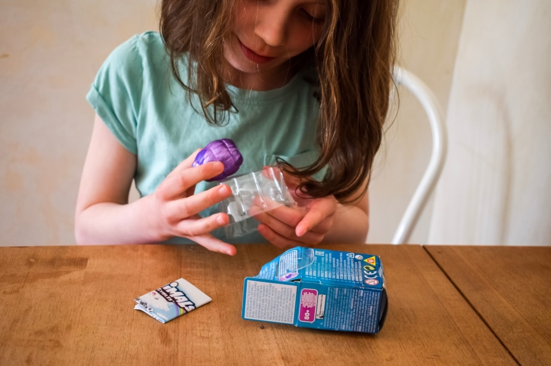 A photograph of a little girl getting a Hatchimals CollEGGtibles Mermal Magic Egg out of the packet - Hatchimals CollEGGtibles Mermal Magic Season 5 Review - Mrs H's favourite things