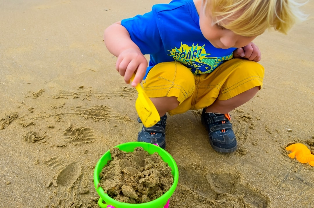 A photograph of a blonde haired little boy building a sand castle on a beach - Konfidence Sand Art Competition 2019 - Mrs H's favourite things