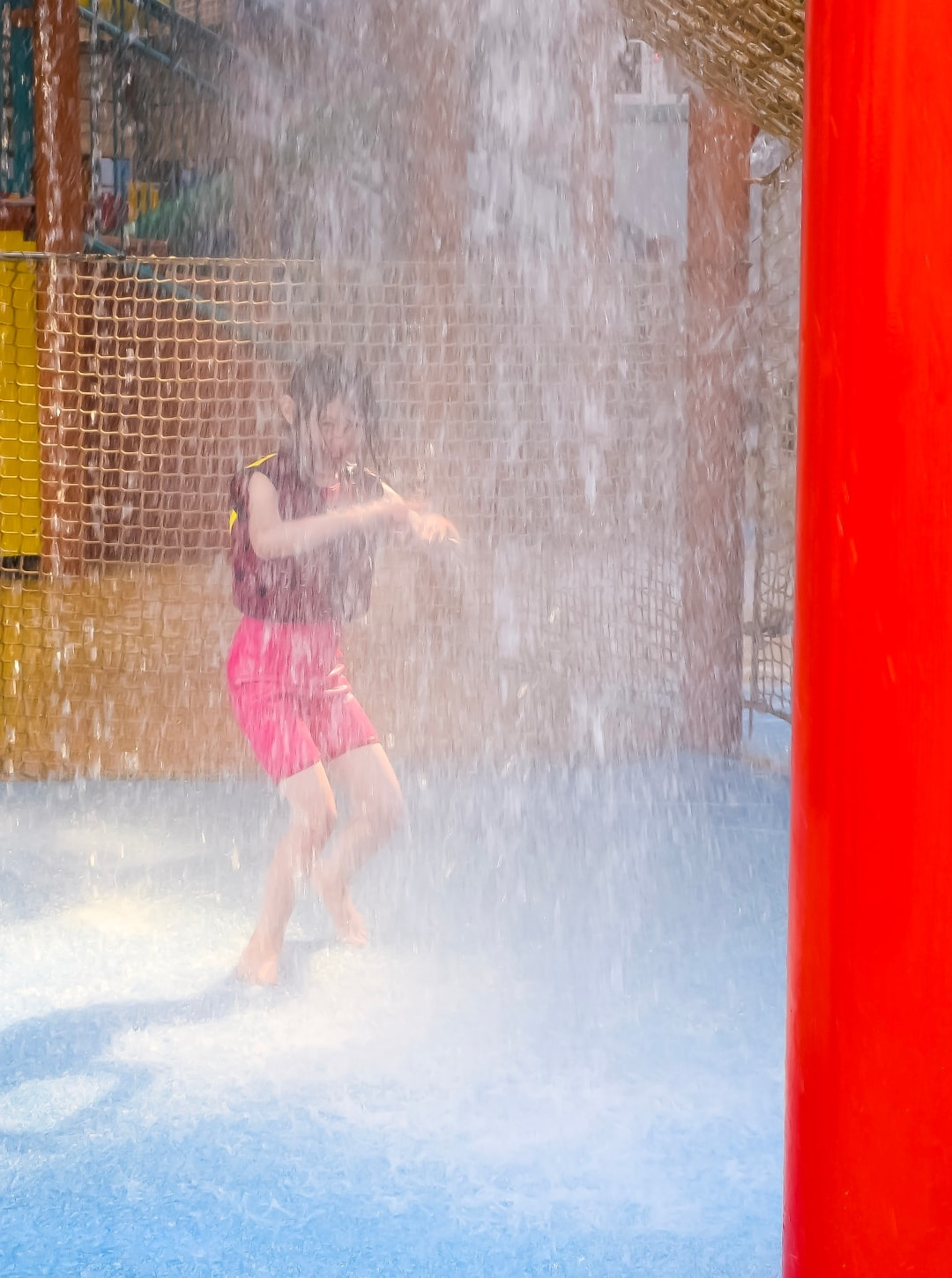 A photograph of a little girl dancing in the water at Splash Landings in Alton Towers - the little girl is wearing the Original Konfidence Swim Jacket and Konfidence Warma Wetsuit - Swimming With Konfidene At Splash Landings - Mrs H's favourite things