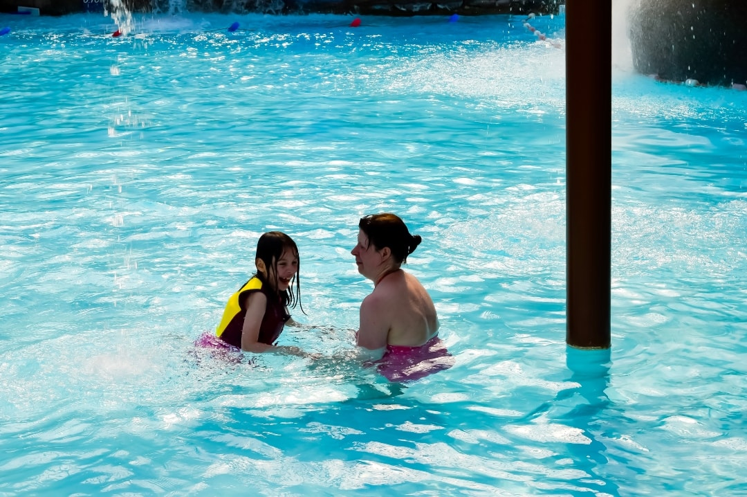 A mother and daughter swimming at Splash Landings in Alton Towers. The little girl is wearing swimwear and buoyancy aids from Konfidence - Swimming With Konfidence At Splash Landings - Mrs H's favourite things