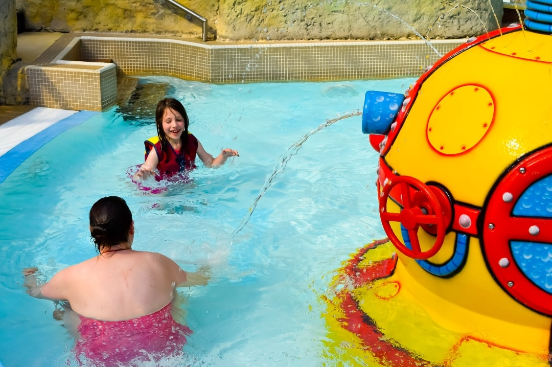A mother and her daughter swimming in the toddler pool at Splash Landings in Alton Towers - the little girl is wearing the Original Konfidence Swimming Jacket and Konfidence Warma Wetsuit - Swimming With Konfidence At Splash Landings - Mrs H's favourite things