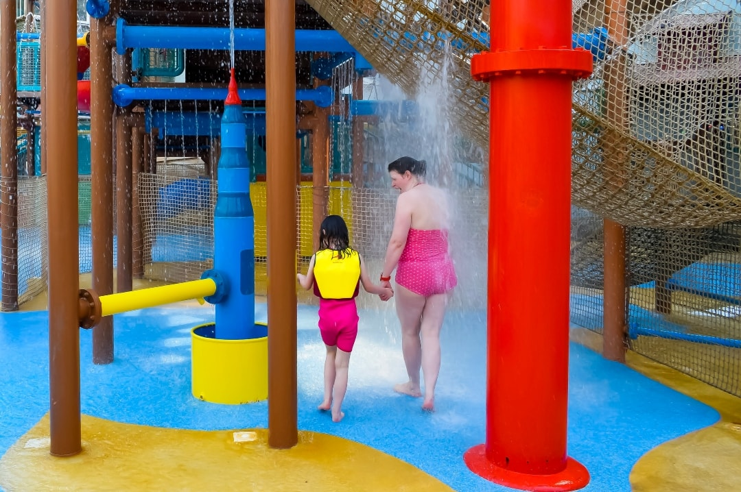 A photograph of a mother and her daughter at Splash Landings in Alton Towers. The little girl is wearing a Konfidence Original Children's Swim Jacket and Konfidence Warma Wetsuit - Swimming With Konfidence At Splash Landings - Mrs H's favourite things