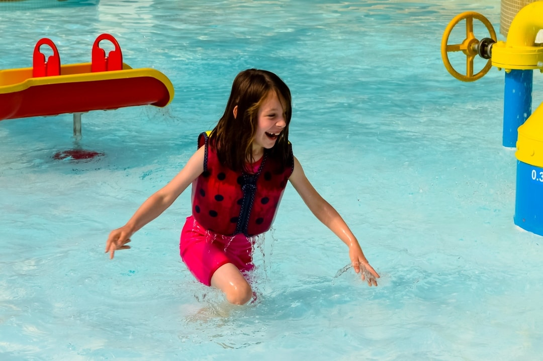 A photograph of a little girl at Splash Landings in Alton Towers wearing a Konfidence Original Swim JAcket and Konfidence Warma Wetsuit - Swimming With Konfidence At Splash Landings - Mrs H's favourite things