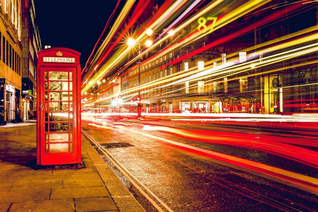 A photograph of a red London telephone box on a street at night time in London with bokeh - The First-Timer's Guide For Travelling To London - Mrs H's favourite things