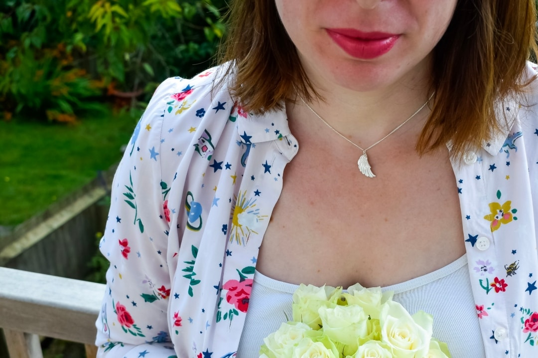 A photograph of a lady wearing a Jana Reinhardt silver wing necklace - the perfect present for a baby loss mama - Silver Wing Necklace By Jana Reinhardt - Mrs H's favourite things