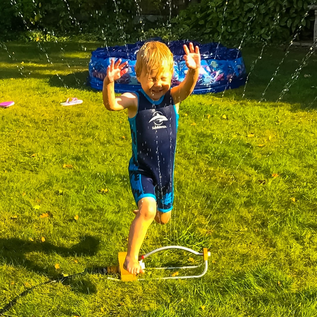 A photograph of a little boy jumping through a sprinkler - Snapshots Of Our Summer - Mrs H's favourite things