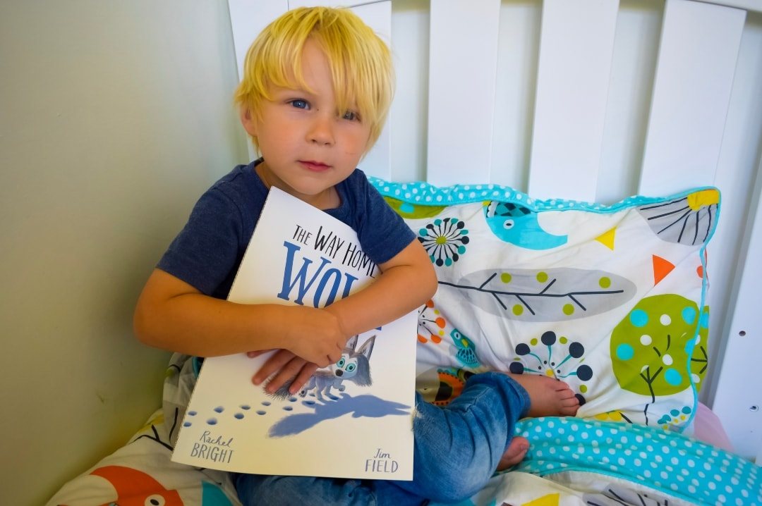 "A photograph of a little boy holding a copy of ""The Way Home For Wolf"" by Rachel Bright and Jim Field - The Way Home For Wilf by Rachel Bright and Jim Field - A Review - Mrs H's favourite things"