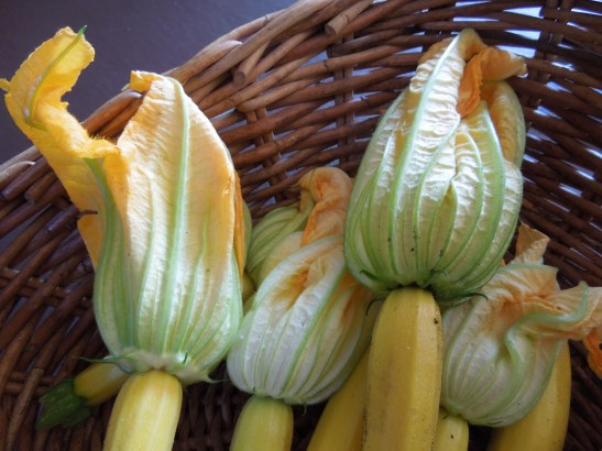 Image of courgettes with their flowers in a basket