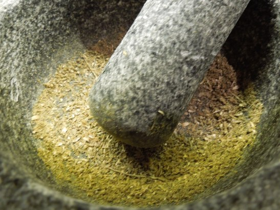 Image of spices being ground in a pestle and mortar