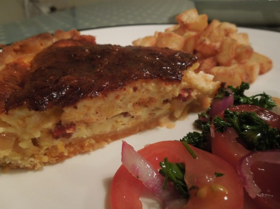 Image of a slice of quiche as part of a meal