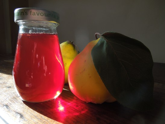 Image of a jar of quince jelly with fresh quinces