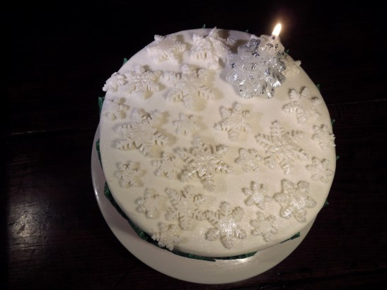 Image of snowflakes and candle on cake
