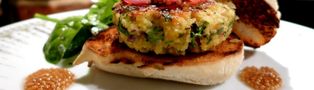 Image of salmon burger in a bun with pickled mustard seeds
