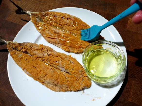 Image of spiced mackerel being brushed with oil