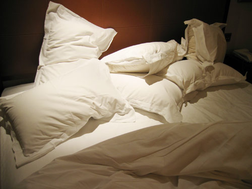 Messy stack of pillows on a bed