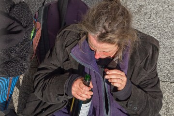 Homeless women addicted to alcohol with a wine bottle