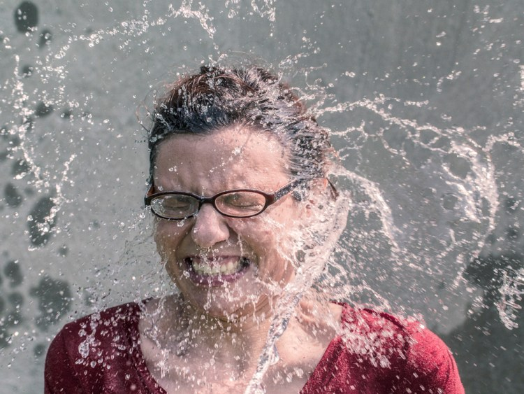 Woman with glasses being sprayed in the face with water