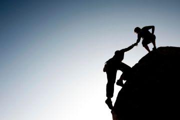 Man getting help climbing up a cliff