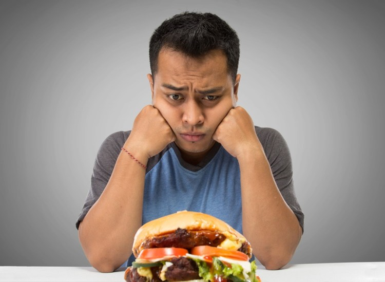 sad man eating fast food burger
