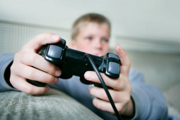 Boy (9-11) playing games console (focus on hands and control)
