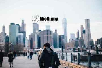 Man walking around manhatten skyline with MicVinny logo in sky